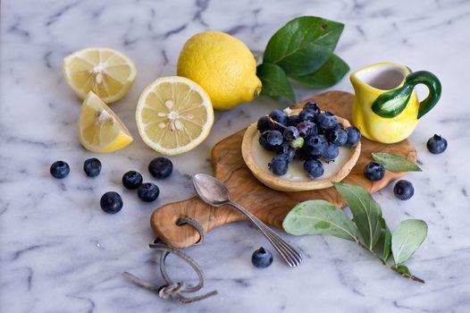 пирожное, лимоны, ягоды, голубика, ложка, листочки, натюрморт