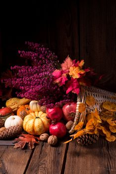Autumn composition of vegetables and fruits, autumn leaves, basket, cones, nuts